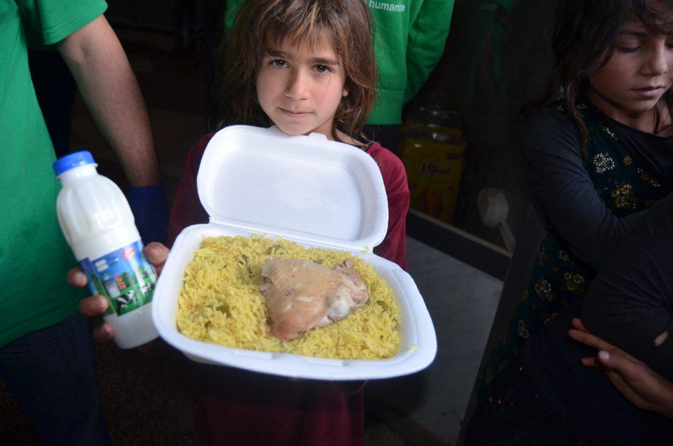 Un jeune enfant syrien montrant le repas qu'il a reçu