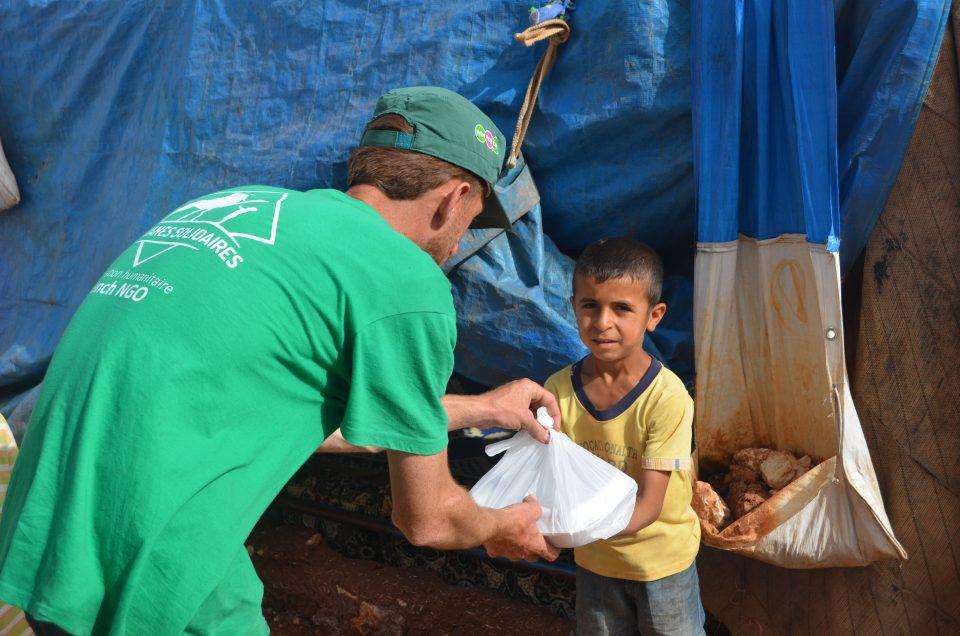 Un bénévoles de Caravanes Solidaires donnant un repas à un petit garçon en Syrie