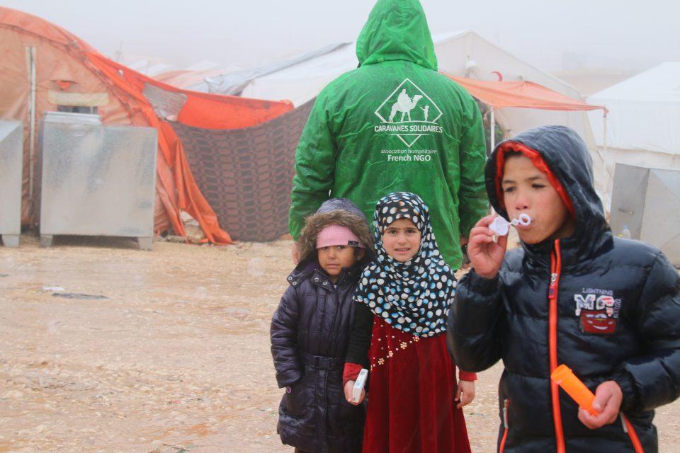 Des enfants syrien avec un bénévoles de Caravanes Solidaires