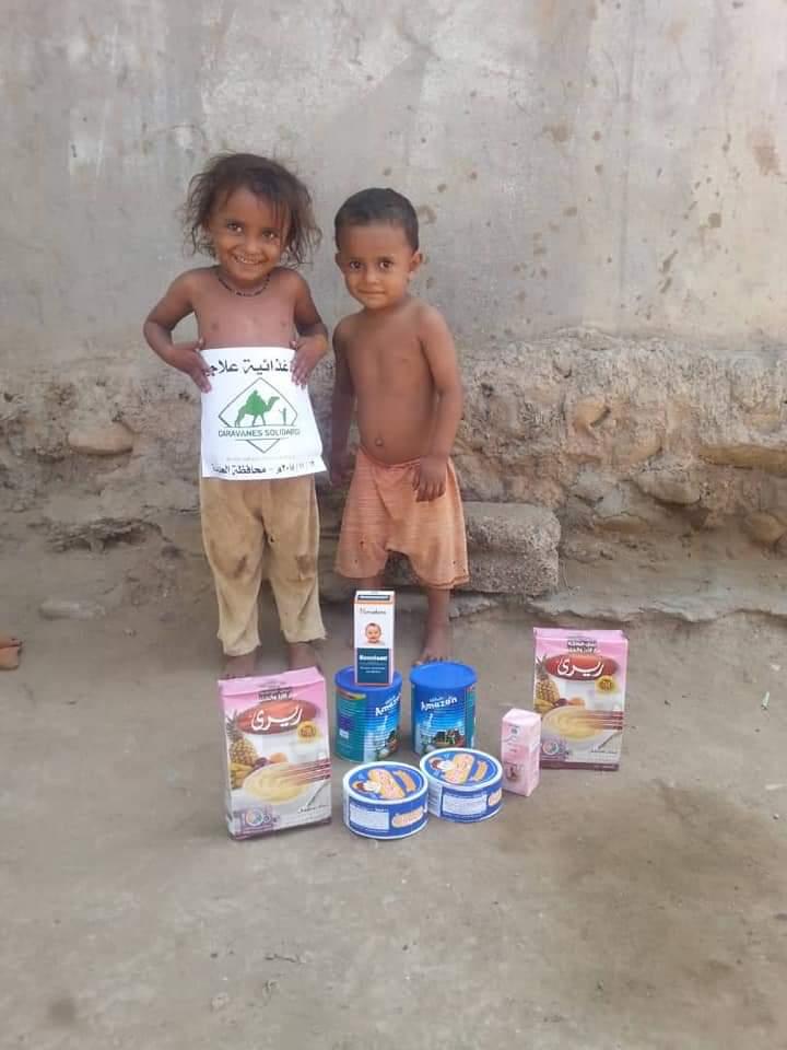Deux enfants posant des produits pour bébés au Yémen - Caravanes solidaires