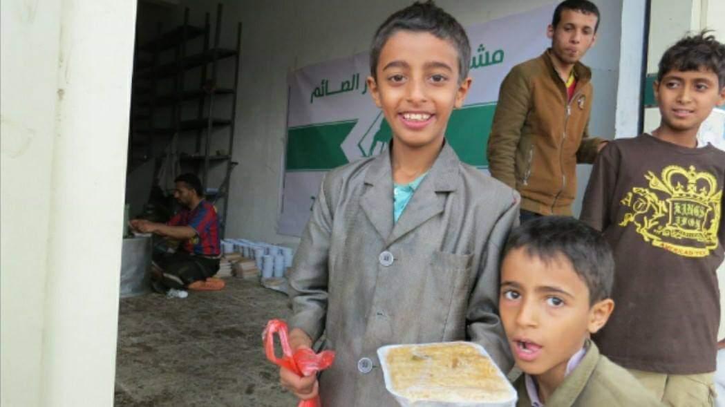 Deux garçon avec un repas de Caravanes solidaires