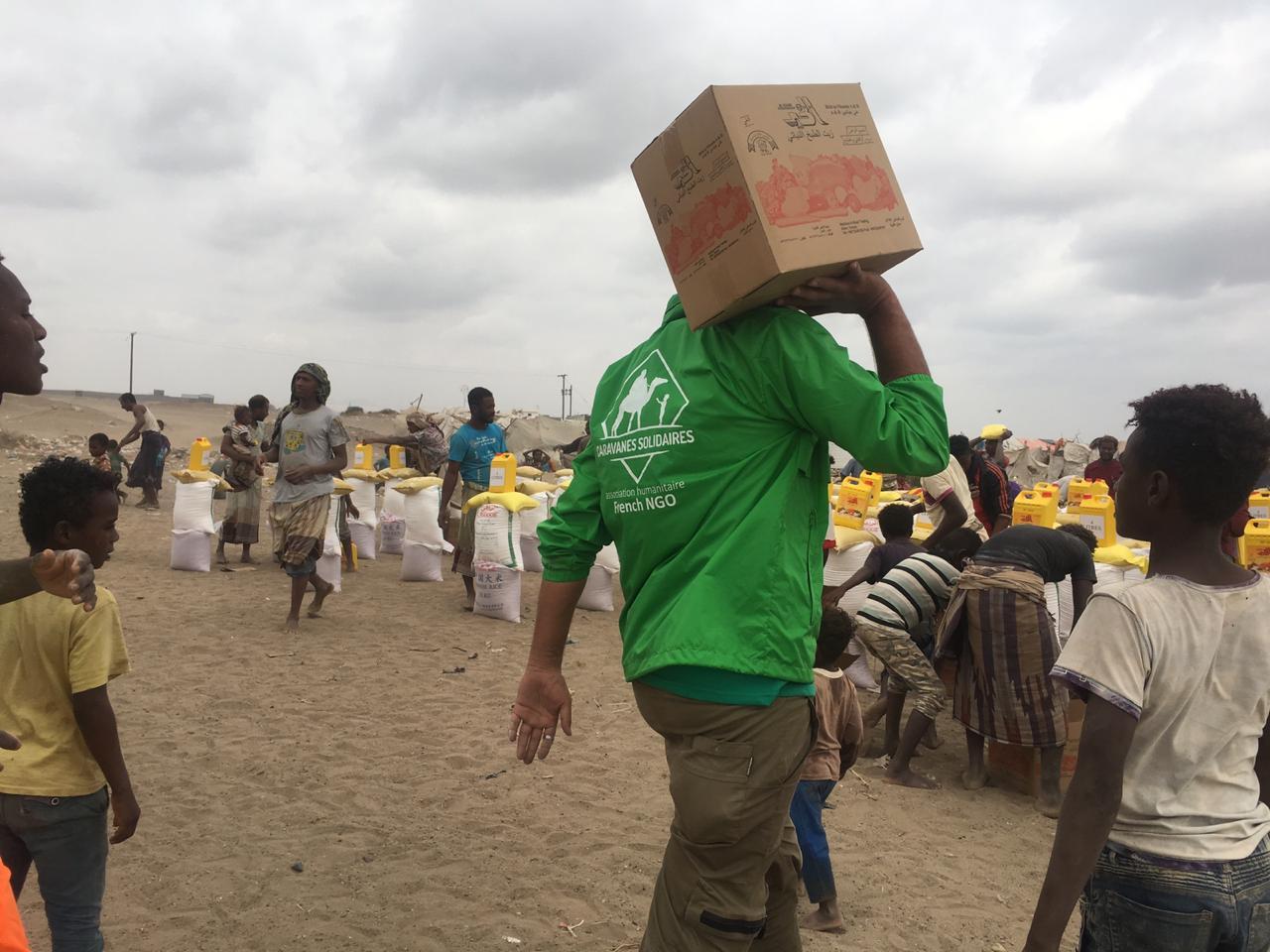 Bénévoles de Caravanes Solidaires distribuant un colis alimentaire au Yémen