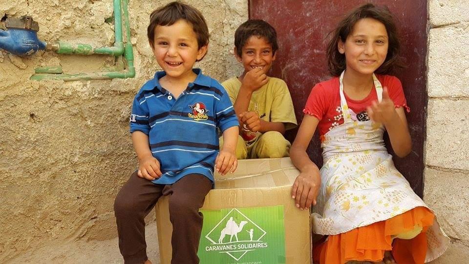 Trois enfants Syrien se tenant à côté d'un colis de Caravanes Solidiares