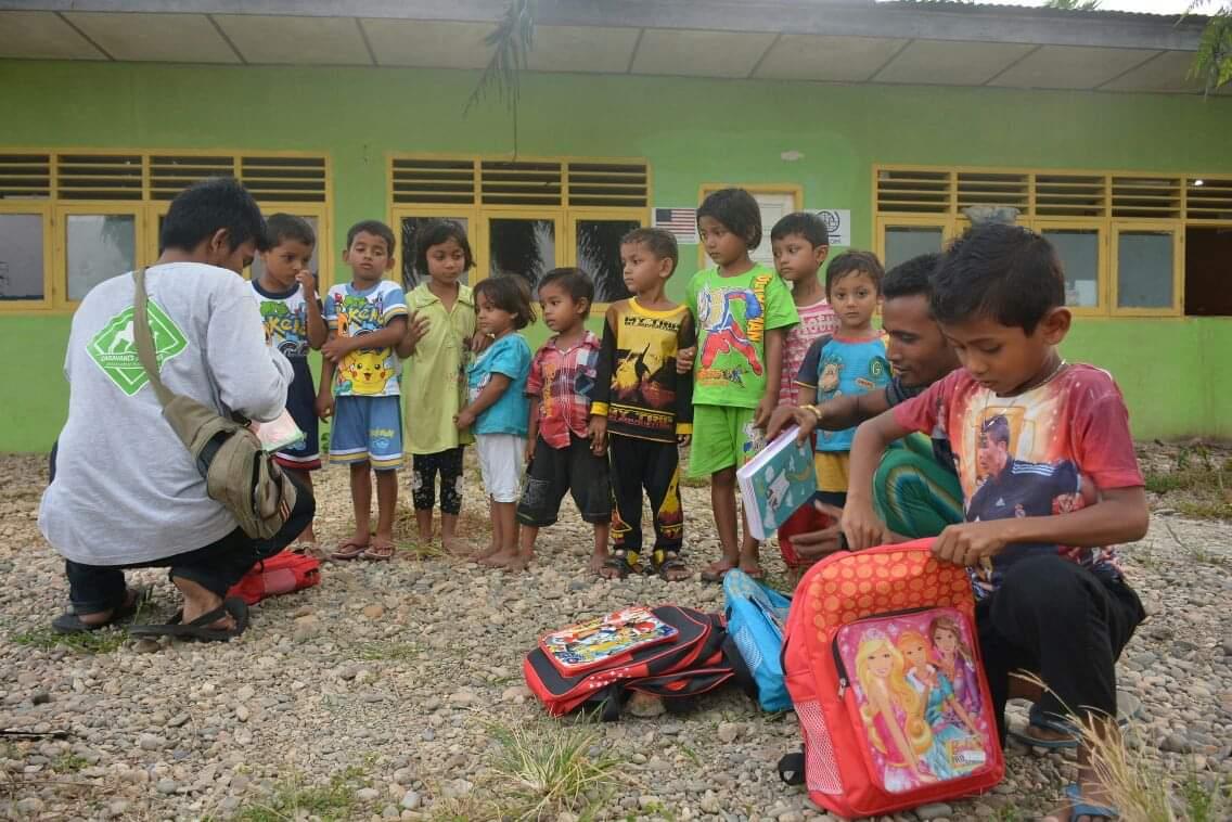Un bénévole de l'association caravanes solidaires avec des écoliers en Indonésie