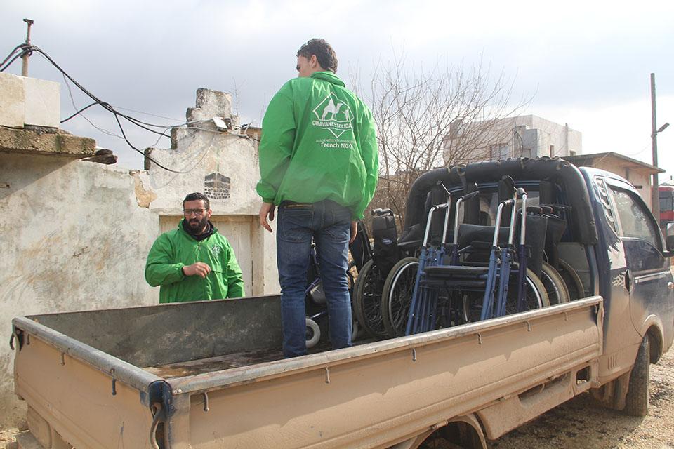 bénévole de l'association caravanes solidaires chargeant des fauteuils roulant en Syrie