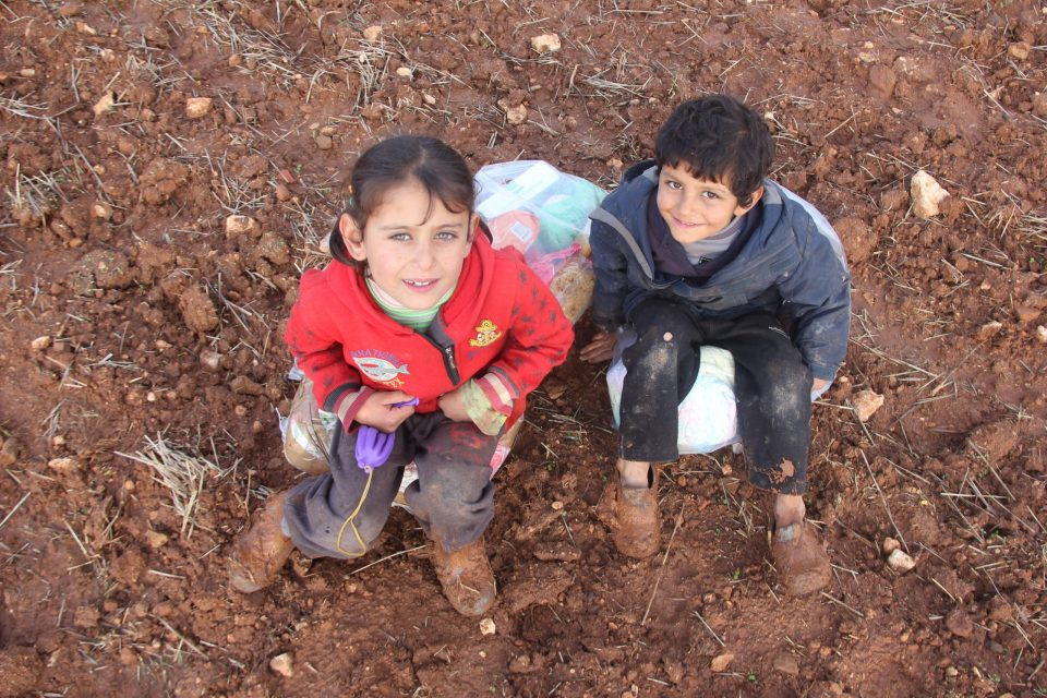 un garçons et un fille assis regardant un objectif qui les surplombenr