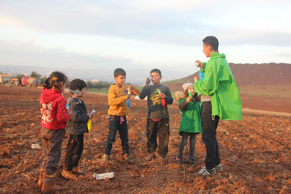 bénévole de l'association caravanes solidaires jouant à faire des bulles de savon avec des enfants